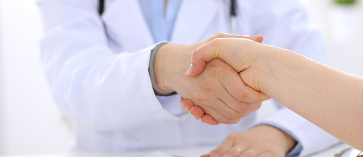 two men, a doctor in a lab coat and a patient shaking hands